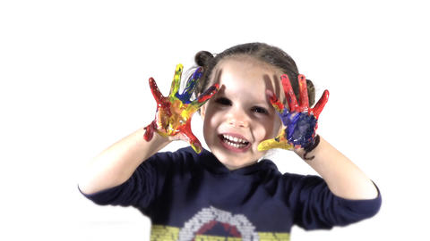 beautiful little girl with hands in the colored paint ビデオ