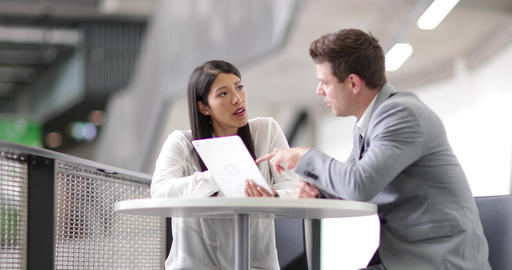 Colleagues in an informal business meeting using a digital tablet GIF
