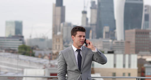 Businessman using smartphone looking out at London city skyline Footage