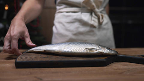 Chef puts herring fish to the wooden board and prepares for cooking, making of Footage