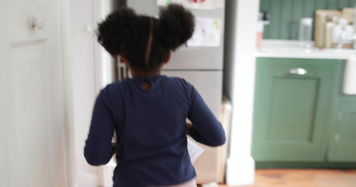 Girl proudly putting school work on refrigerator Footage