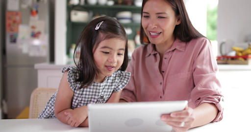 Mother teaching Daughter how to use digital tablet Footage