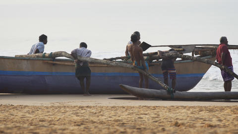 Local fishermen straining to pull wooden boat ashore at Galle. Sri Lanka Live Action
