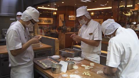 Food service workers preparing Chinese dumplings in a restaurant Footage