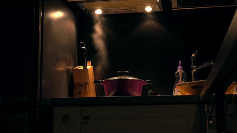 Steaming pan on the cooker in dark kitchen Footage