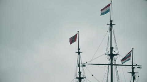 Waving flags of Netherlands and Amsterdam on the masts of an old ship memorial Footage