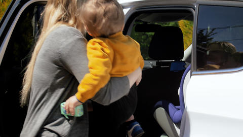 4k footage of young mother seating her toddler son in child car seat Live Action