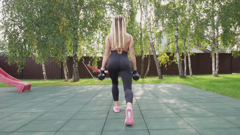 Muscular woman athlete doing walking lunges with dumbbells on a sports ground Footage