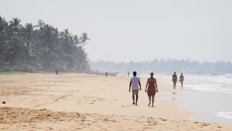 Happy tourists strolling along a popular beach in Hikkaduwa Live Action