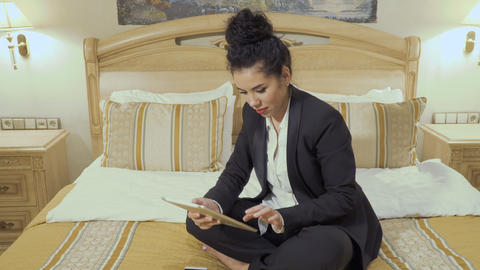 Attractive business lady talks on phone and uses digital tablet in a hotel room Footage