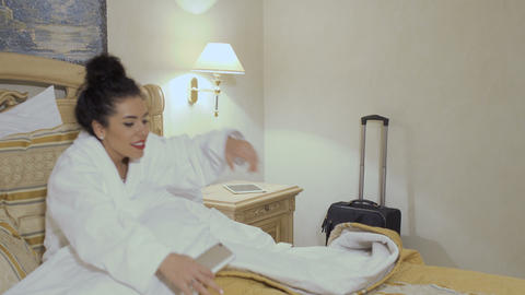 Attractive lady in white bathrobe goes to sleep in a hotel room Live Action