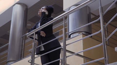 Attractive lady in black suit leans on railing and talks on phone Footage