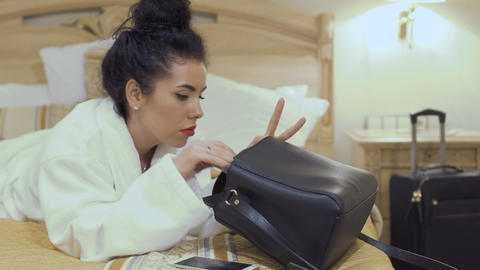Beautiful brunette searches something in her bag Footage