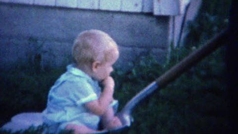 1961: Baby sitting on coal shovel pulled around yard by father Footage