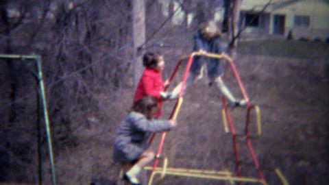 1961: Girls playing backyard climbing playground steel structure Footage