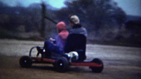 1961: Young sister driving nervous brother go kart circle muddy track Footage