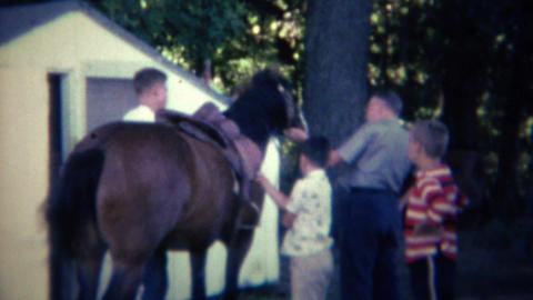 1962: Family readies wild nervous horse for recreational riding pleasure Footage