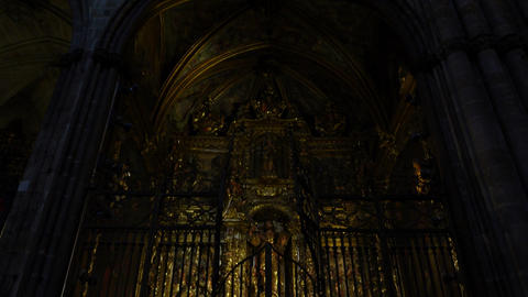 Dim illuminated apse iconostasis at Barcelona Cathedral, tilt down shot Live Action