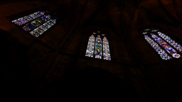 Many stained-glass windows at neo-Gothic Cathedral Ambulatory, low angle panning Footage