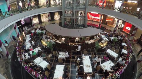 Guests enjoy fine dining in atrium restaurant at Shoppes at Marina Bay Sands Live Action