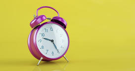 Violet metal alarm clock time lapse copy space yellow background Animation