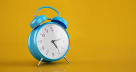 Blue vintage alarm clock time lapse copy space warm yellow background Animación