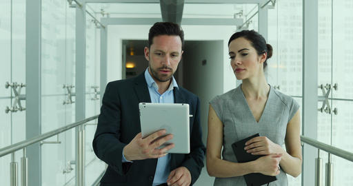 Business colleagues looking at digital tablet together Live Action
