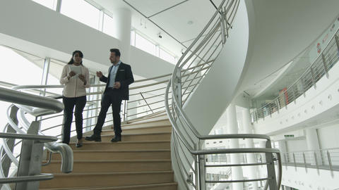 Business colleagues walking down spiral staircase Footage