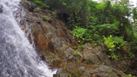 Following Tropical Waterfall over Rocks from First Person View Footage