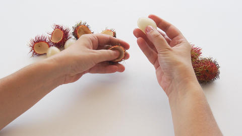 Hands Opening Rambutan Fruit on a White Table. 4k footage 2160p Footage