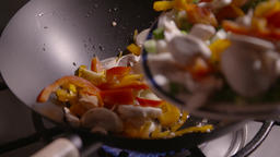 Slow motion clip of sliced vegetables being poured into a wok ready for frying Image