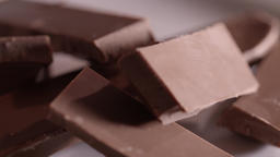 Pieces of chocolate rotating on a plain background Filmmaterial