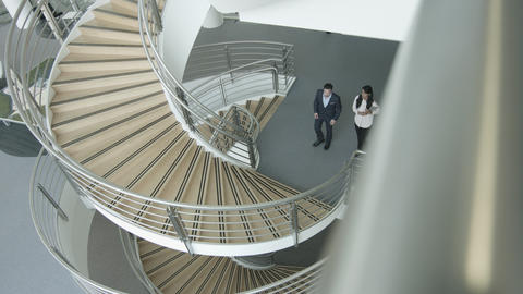 Overhead business colleagues walking up spiral staircase discussing work Footage