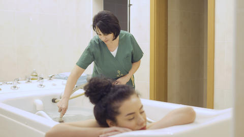 Cheerful woman with red lips relaxing during the procedure of hydromassage Footage