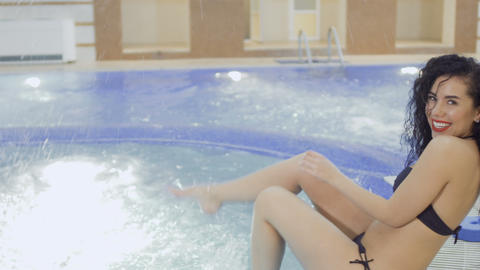 Young beautiful woman splashes water in the swimming pool Footage