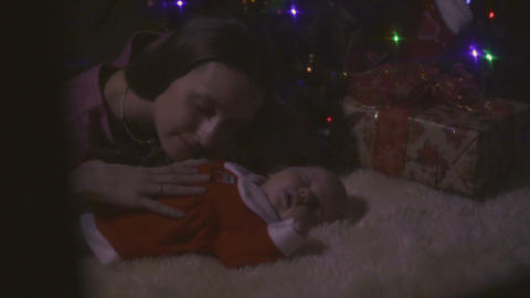 Young mother kisses her little sleeping daughter near Christmas tree Archivo
