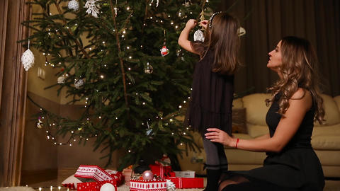 Mom and daughter decorate a Christmas tree with colored balls Footage