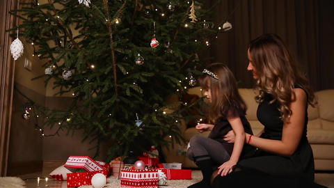 Mom and daughter dress up a Christmas tree on Christmas Eve Live Action