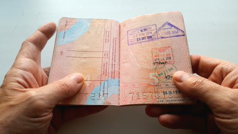 Close-up of a foreign passport in the hands of a man Footage
