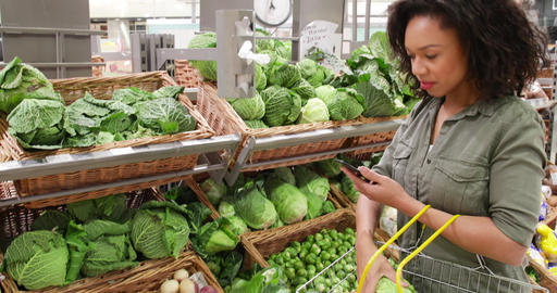 Woman in grocery store using smartphone Live Action
