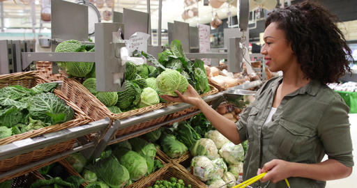Woman buying vegetables in grocery store Footage