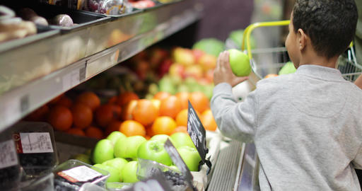 Mother and son buying fruit and vegetables in grocery store Footage