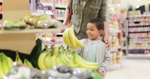 Boy picking up bananas in grocery store Footage