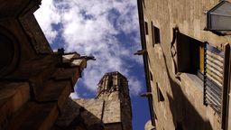 Gothic Church bell tower and walls against blue sky, low angle dolly shot Footage