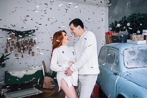 Happy pregnant white woman and man are hugging near the car, stylish future Fotografía