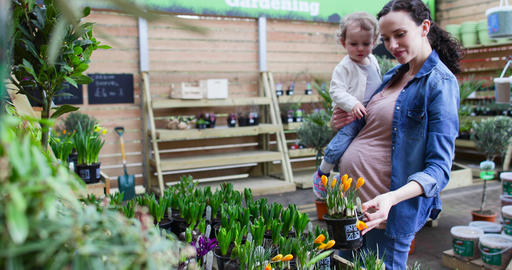 Pregnant mother with daughter at garden centre Footage