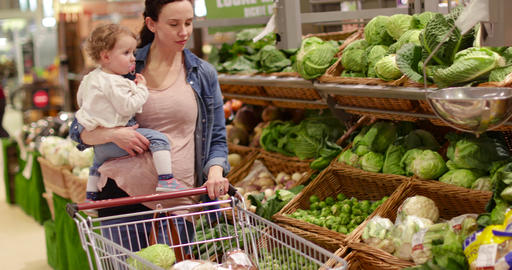 Mother and daughter buying vegetables in grocery store Footage