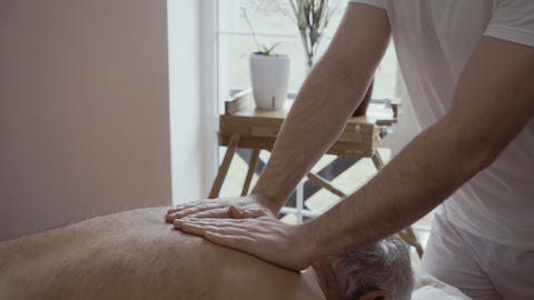 Professional masseur massages old man's back Footage