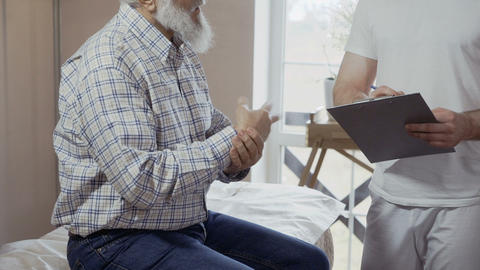 Old man complain to doctor about pain in elbow and wrist Footage