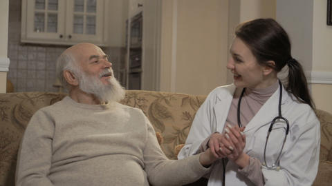 Health visitor talks with senior man at the sofa Footage